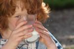 Meisje drinkt lekkere melk in het gras
